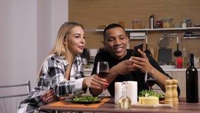 Herrliche zwischen verschiedenen Rassen Paare, die Kerzenlicht Telefonschirm betrachtend zu Abend essen stock footage