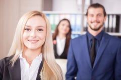 Herrlicher blonder Manager vor ihrem Team Stockbild