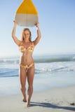 Herrlicher blonder Surfer im Bikini, der ihr Brett hält Stockfoto
