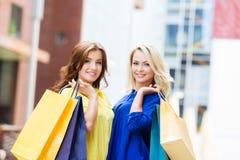 Herrlicher Brunette und blondes Sein glücklich mit Einkaufstaschen Stockfotografie