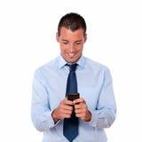 Herrlicher erwachsener Mann, der mit seinem Mobiltelefon simst Lizenzfreie Stockfotografie