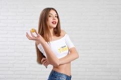 Herrlicher junger Kaukasier in der weißen Erntespitze mit bitcoin Logo, das mit goldenem bitcoin aufwirft Stockfotografie