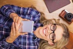 Herrlicher lächelnder blonder Hippie, der Smartphone verwendet Stockfoto