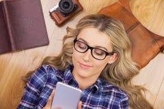 Herrlicher lächelnder blonder Hippie, der Smartphone verwendet Stockfotos