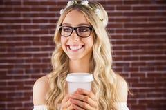 Herrlicher lächelnder blonder Hippie mit Blumenstirnband und Kaffee Lizenzfreies Stockbild