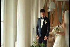 Herrlicher lächelnder Bräutigam Gut aussehender Mann in einer Reihe mit einem Knopfloch am Fenster im Luxusrestaurant stock footage