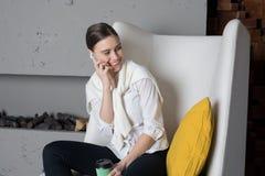 Herrlicher netter weiblicher Hochschulstudent, der über modernes Zelltelefon nennt lizenzfreie stockfotos