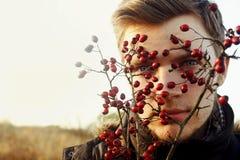 Herrlicher stilvoller schöner hübscher blonder Junge und rote Beeren O Lizenzfreies Stockbild