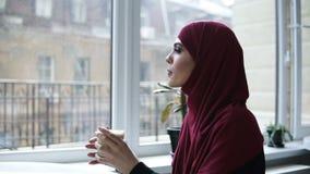 Herrliches arabisches Mädchen trinkt Cappuccino Zuhause Zeitlupegesamtlänge stock video