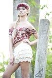 Herrliches blondes in der roten Blumen-Krone Stockfotografie