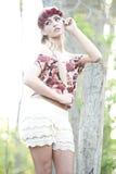 Herrliches blondes in der roten Blumen-Krone Stockfoto