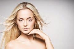 Herrliches blondes mit der reinen Haut, die auf grauem Hintergrund aufwirft Stockbild