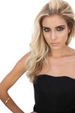 Herrliches blondes Modell im schwarzen Kleid, das Kamera betrachtend aufwirft Stockfotografie