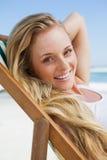 Herrliches blondes Sitzen am Strand, der an der Kamera lächelt Lizenzfreie Stockbilder