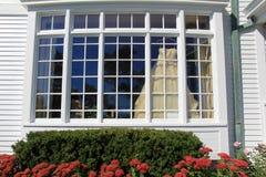 Herrliches Hochzeitskleid, das vom Bildfenster des Hauses hängt Stockfotografie