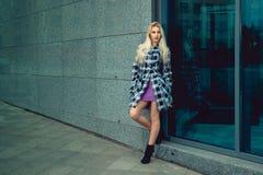 Herrliches junges blondes Mode-Modell, das draußen aufwirft und a schaut Stockfoto