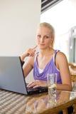 Herrliches junges blondes, Spaß mit Laptop habend. Stockfoto