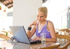 Herrliches junges blondes, Spaß mit Laptop habend. Lizenzfreie Stockfotografie