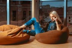 Herrliches junges blondes Unterhaltungstelefon und Aufstellung auf orange Couch n Lizenzfreie Stockbilder