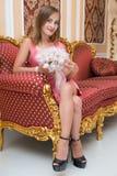 Herrliches junges Mädchen, das auf luxuriösem Sofa sitzt und Blumen hält stockbilder