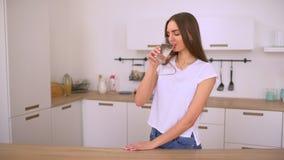Herrliches junges Mädchen hält gesund, indem sie zuhause ein Glas Wasser trinkt und lächelt stock video