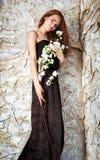Herrliches junges Weinlesemädchen, das Blumen hält Stockfoto