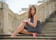 Herrliches Mädchen, das auf Marmortreppe sitzt Stockfotos
