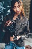 Herrliches Mädchen, das Belichtungsmesser- und Fotokamera, Hippie-Art halten aufwirft Stockfoto