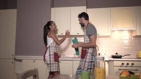 Herrliches Paar ist gleichzeitig tanzend und arbeitend Mädchen gibt Kerlgläser Er trocknet sie oben Auch sie sind