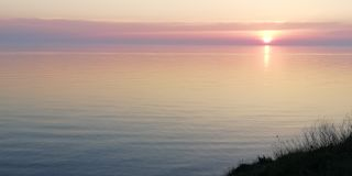 Herrliches Rosa und lila Sonnenuntergang über der ruhigen Ausdehnung des Meeres lizenzfreie stockfotografie