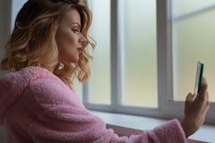 Herrliches sexy blondes Herstellungsselfie nahe Fenster Stockfotografie