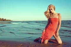 Herrliches sexy dünnes blondes Modell im korallenroten roten trägerlosen Kleid, das auf Knien im Meerwasser steht und beiseite sc lizenzfreies stockbild