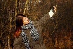 Herrliches stilvolles schönes glückliches Brunettemädchen, das selfie nimmt und Stockbild