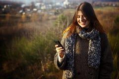 Herrliches stilvolles schönes glückliches Brunettemädchen, welches das te betrachtet Lizenzfreie Stockfotos