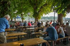 People having lunch in a biergarten. Herrsching,Germany-August 20,2018: People sit in a biergarten talking to friends stock photo