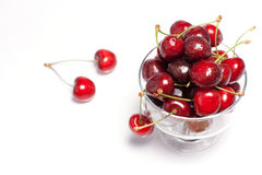 Сherry on the table and in the cup. Сherry in a clear bowl and a few berries on a white background close Stock Photos