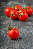 Сherry tomatoes. Red cherry tomatoes in water drops on the black granite surfaces Royalty Free Stock Photography
