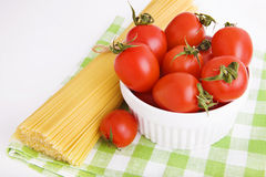 Herry tomatoes in a bowl and  spaghetti on green Stock Image