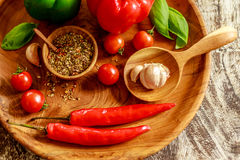 Сherry tomatoes, garlic, chili, basil leaves, red and green capsicums, mix of dry spices in a wooden pot over wooden table Royalty Free Stock Photography