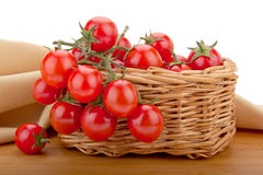 Сherry tomatoes isolated in a basket. Photo depicting a basket of tomatoes and a tablecloth Royalty Free Stock Photo