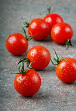 Сherry tomatoes in water drops. Red cherry tomatoes in water drops on the dark surfaces Stock Image