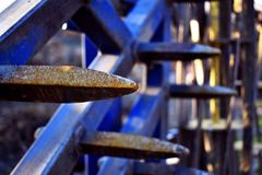 Herse bleue, machine agricole, avec les transitoires rouillées photographie stock