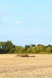 Herse parmi la chaume sur les terres cultivables moissonnées Image libre de droits
