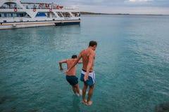 09 20 2008, Hersonissos, Crete, Grecja Młodzi człowiecy skacze w wodę na tle statek fotografia stock
