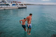09.20.2008, Hersonissos, Crete, Greece. A young men jumping into water on background of the ship. stock photography
