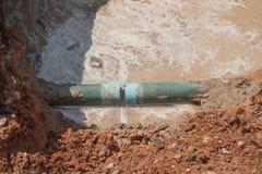Herstel de loodgieterswerk gebroken pijp en waterstroom in gat stock foto