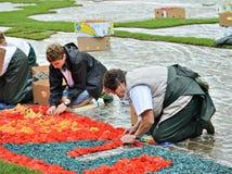 Herstellen des Blumen-Teppichs auf Grand Place während des Regens Lizenzfreies Stockfoto