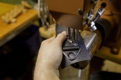 Herstellen eines Kasten-Stiches auf schwarzem Leder lizenzfreies stockfoto