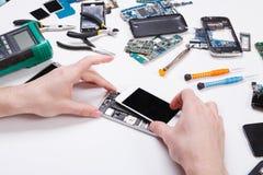 Hersteller demonterende telefoon voor het inspecteren royalty-vrije stock foto's