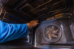 Hersteller die de motorventilator binnen in de oven bevestigen stock foto